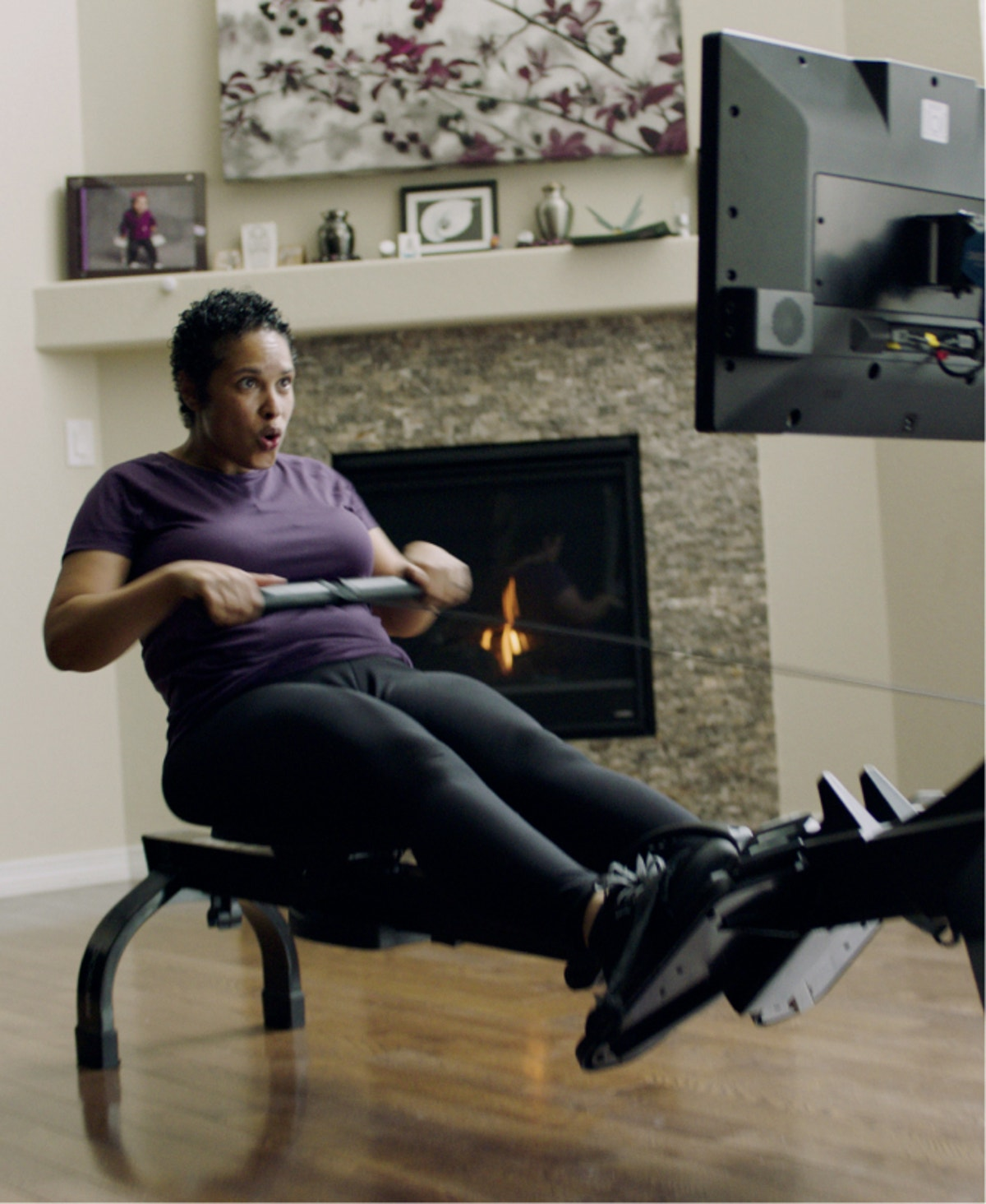 Woman intensely rowing on iFIT rowing machine.