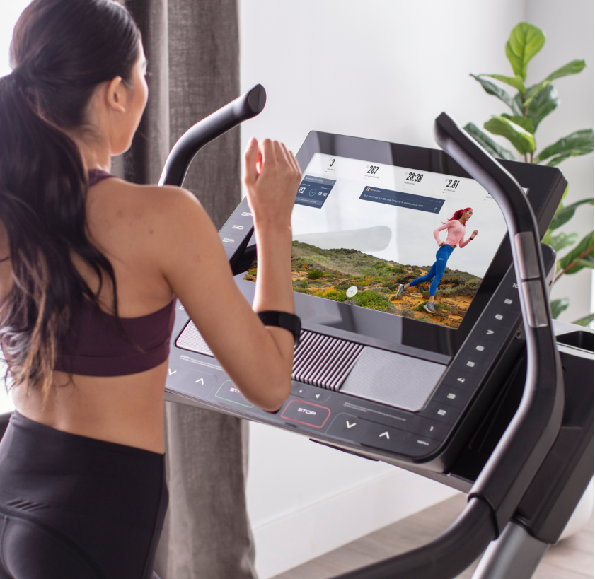 Woman does an iFIT running workout on a treadmill