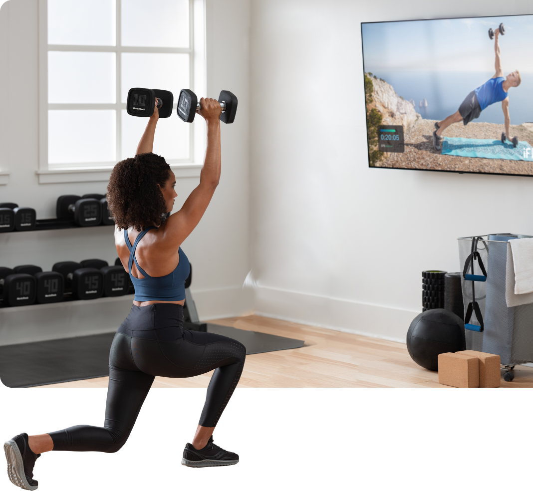 Woman exercises with dumbells while watching iFIT on TV