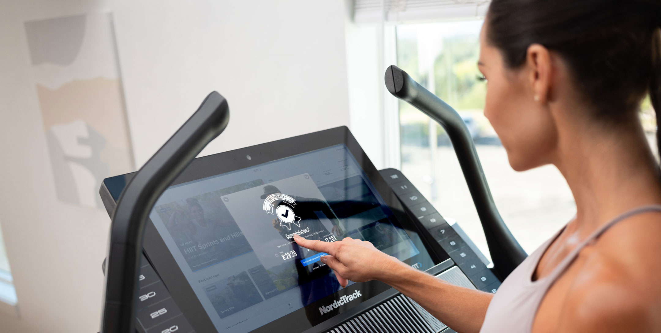 Woman uses screen on NordicTrack treadmill