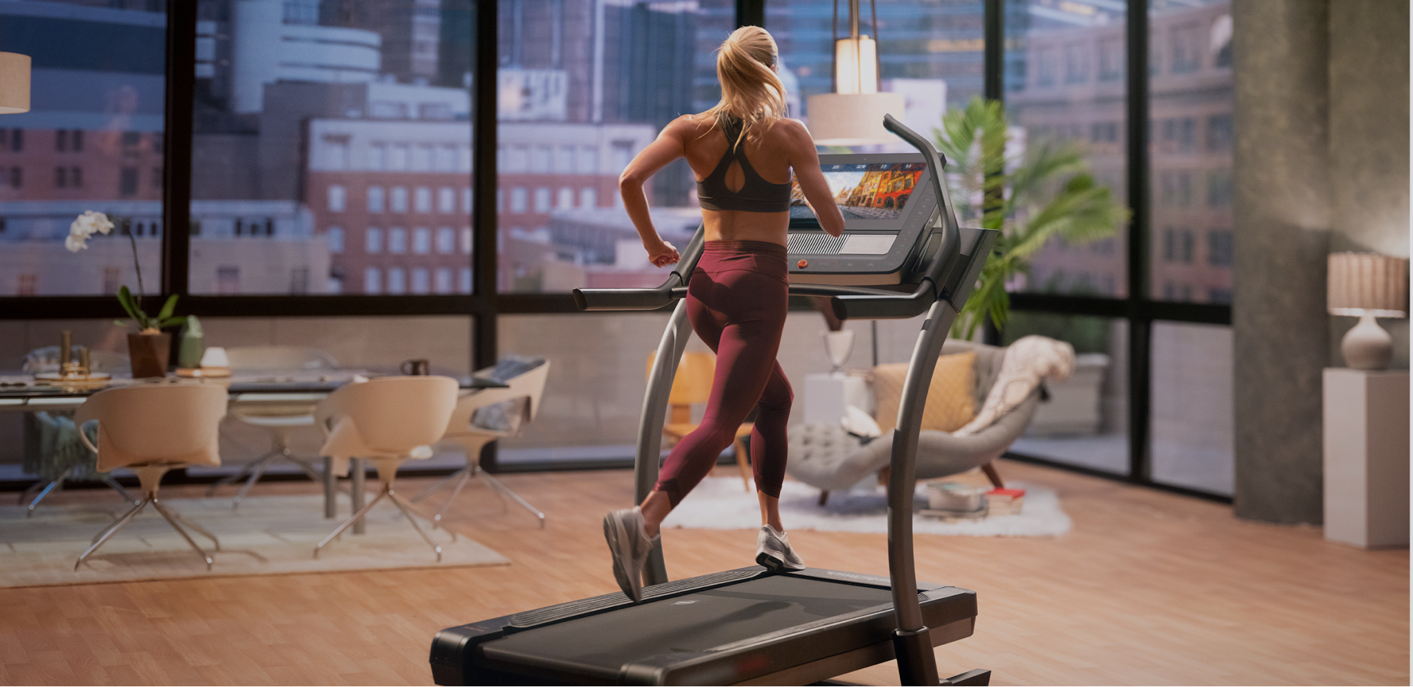 Woman does an iFIT running workout using Google Maps on her treadmill