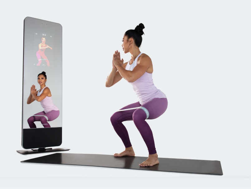Woman using interactive fitness mirror