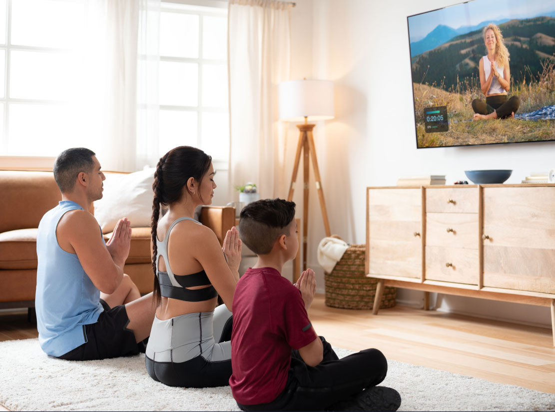 Family does a meditation class using the iFIT TV app