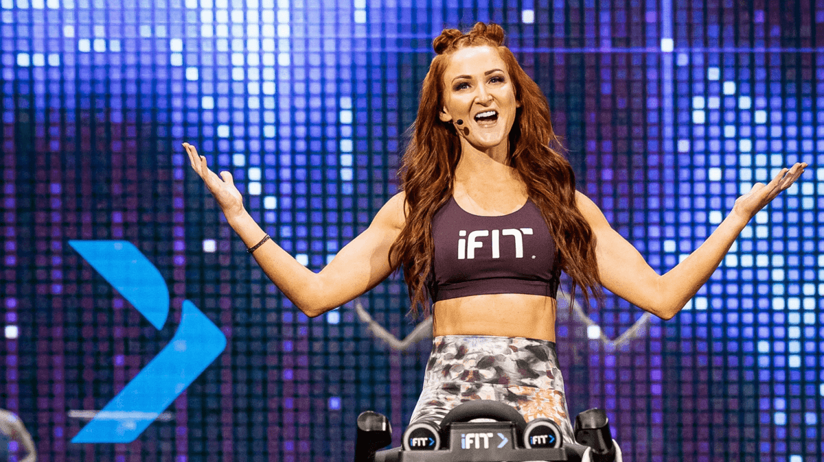 Personal trainer coaches an iFIT cycling workout