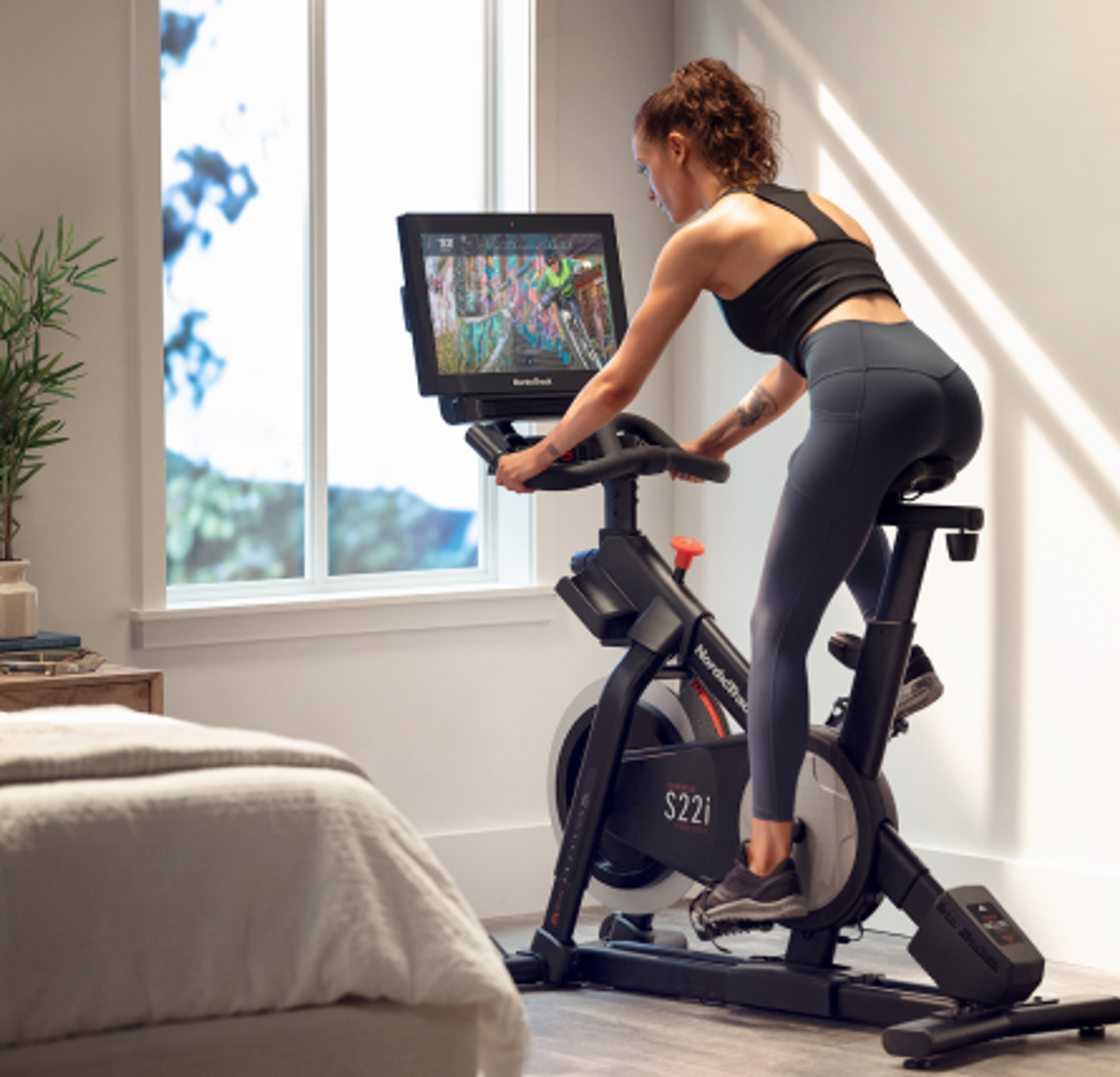 Woman does an iFIT workout class on her bike