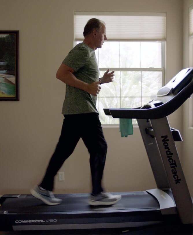 Man running on iFIT treadmill.