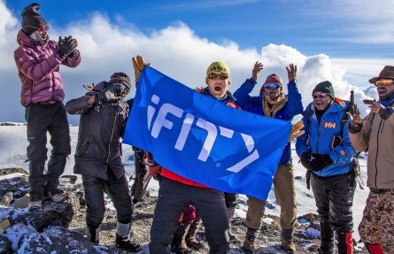 Group of people on top of mountain holding iFIT flag
