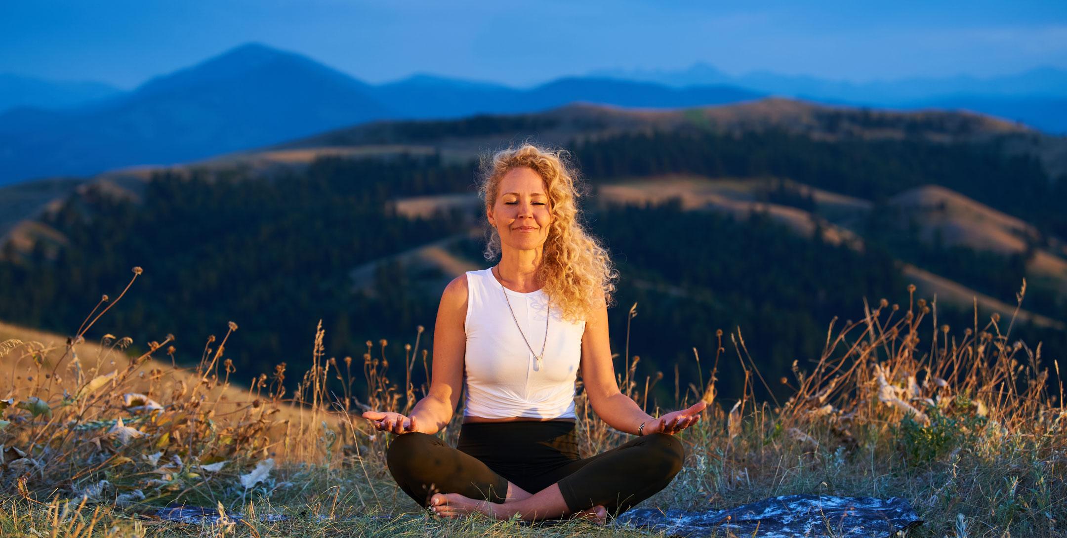 Woman meditates on blanket in a field