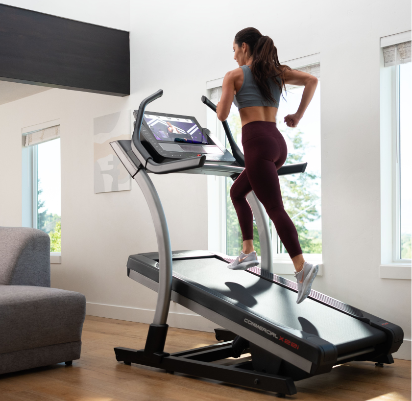 Woman does an iFIT treadmill workout with LiveAdjust