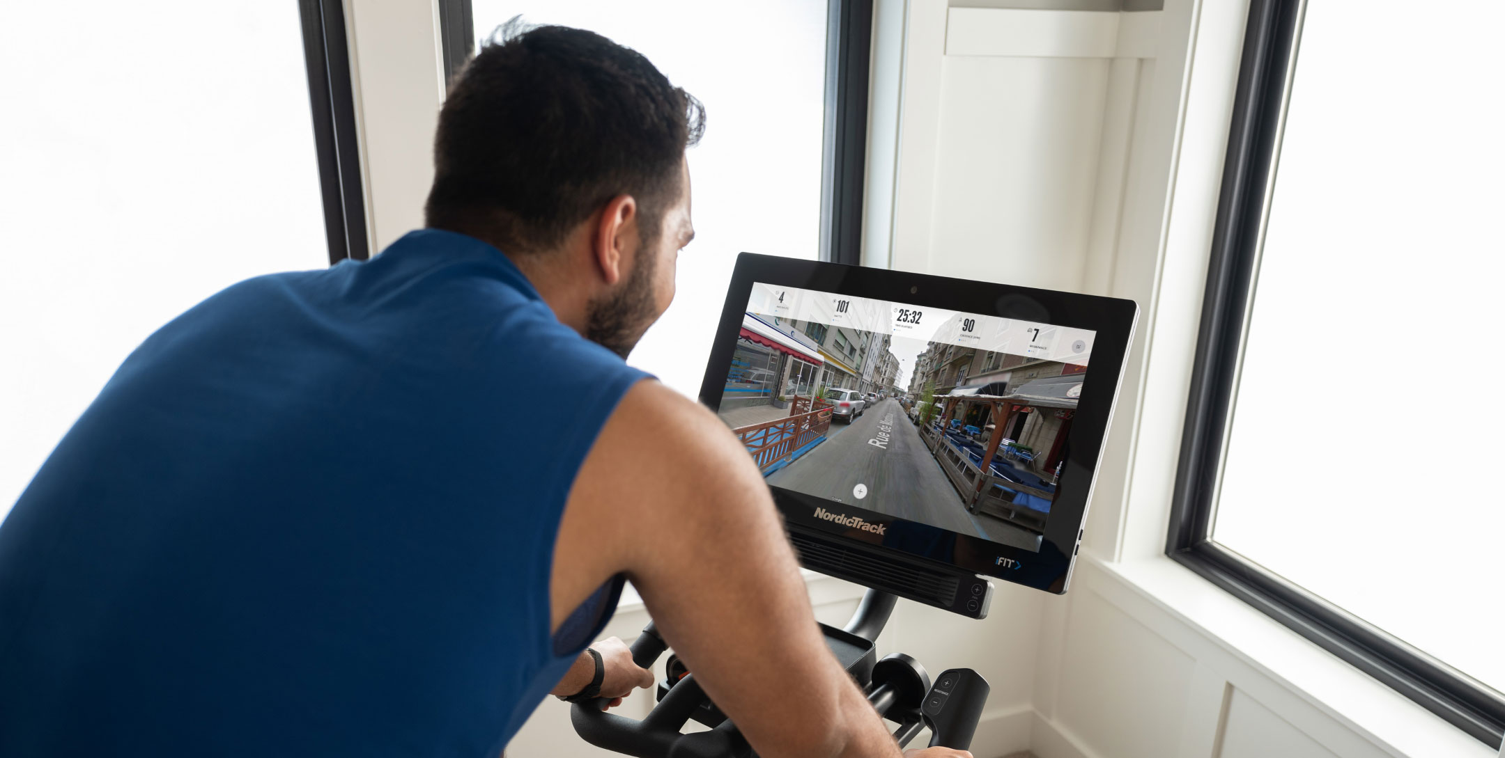 Man rides NordicTrack bike while viewing Google Maps