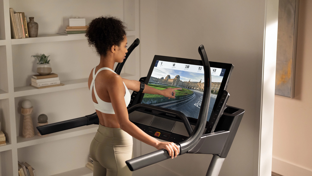 Woman touches her iFIT-enabled treadmill's screen during a running workout