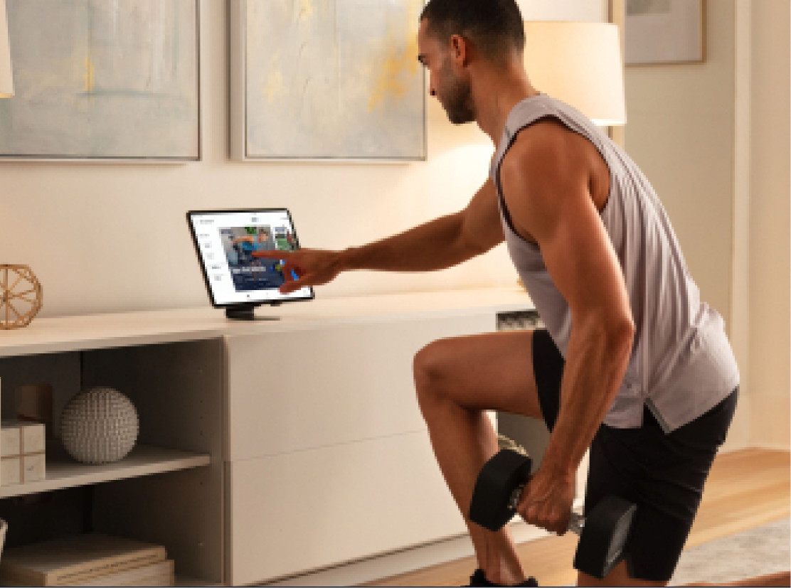 Man does an iFIT weight lifting workout using his tablet