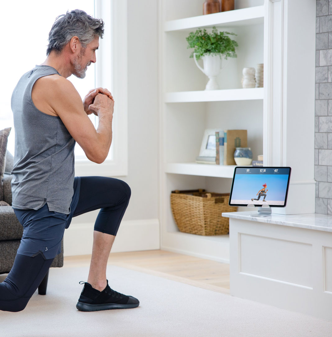 Man does an iFIT bodyweight workout using his tablet