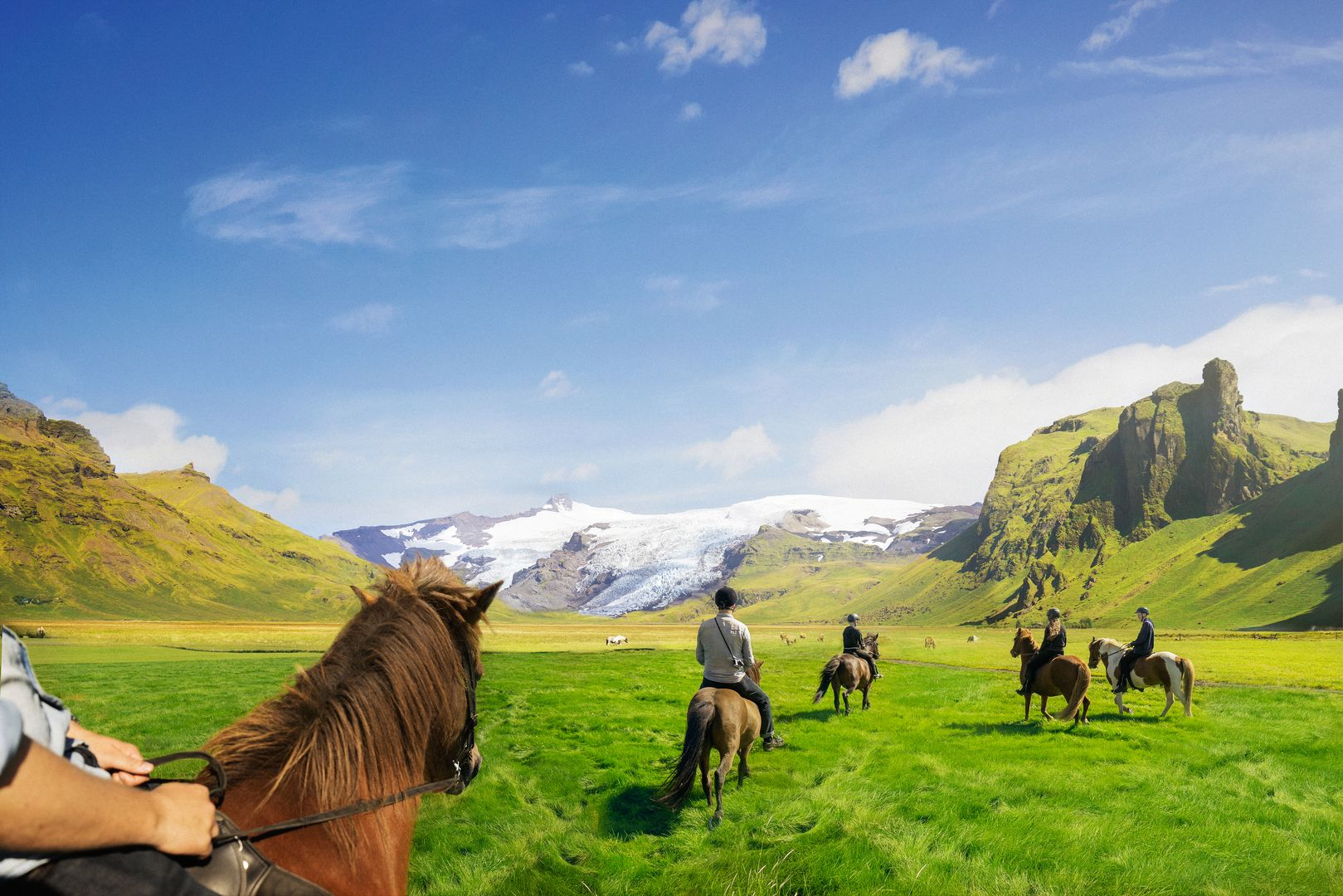 a group of horses riding through the Icelandic countryside