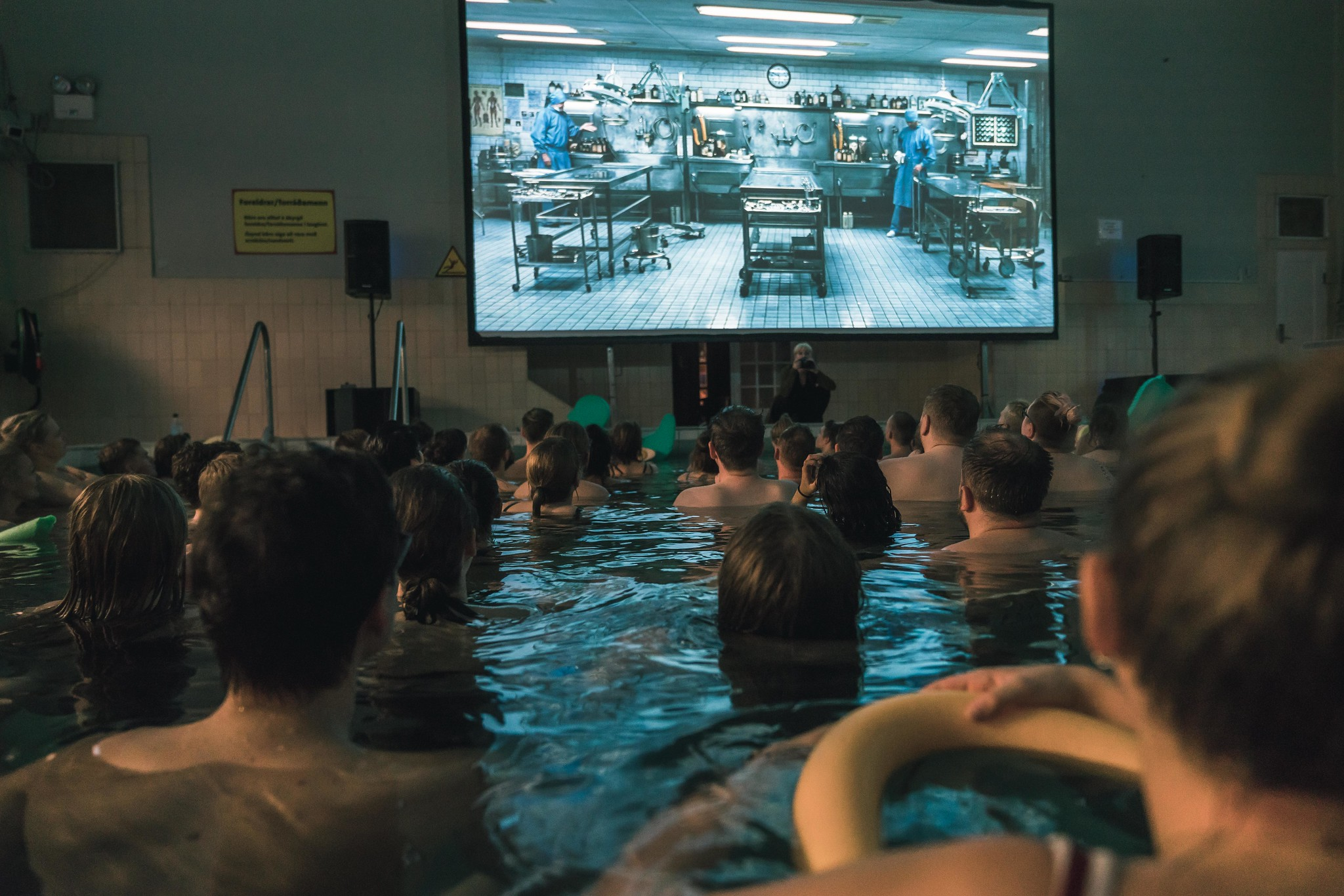 A group of people bathing in a public pool with a screen overhead that is playing a film as part of Riff International Film Festival