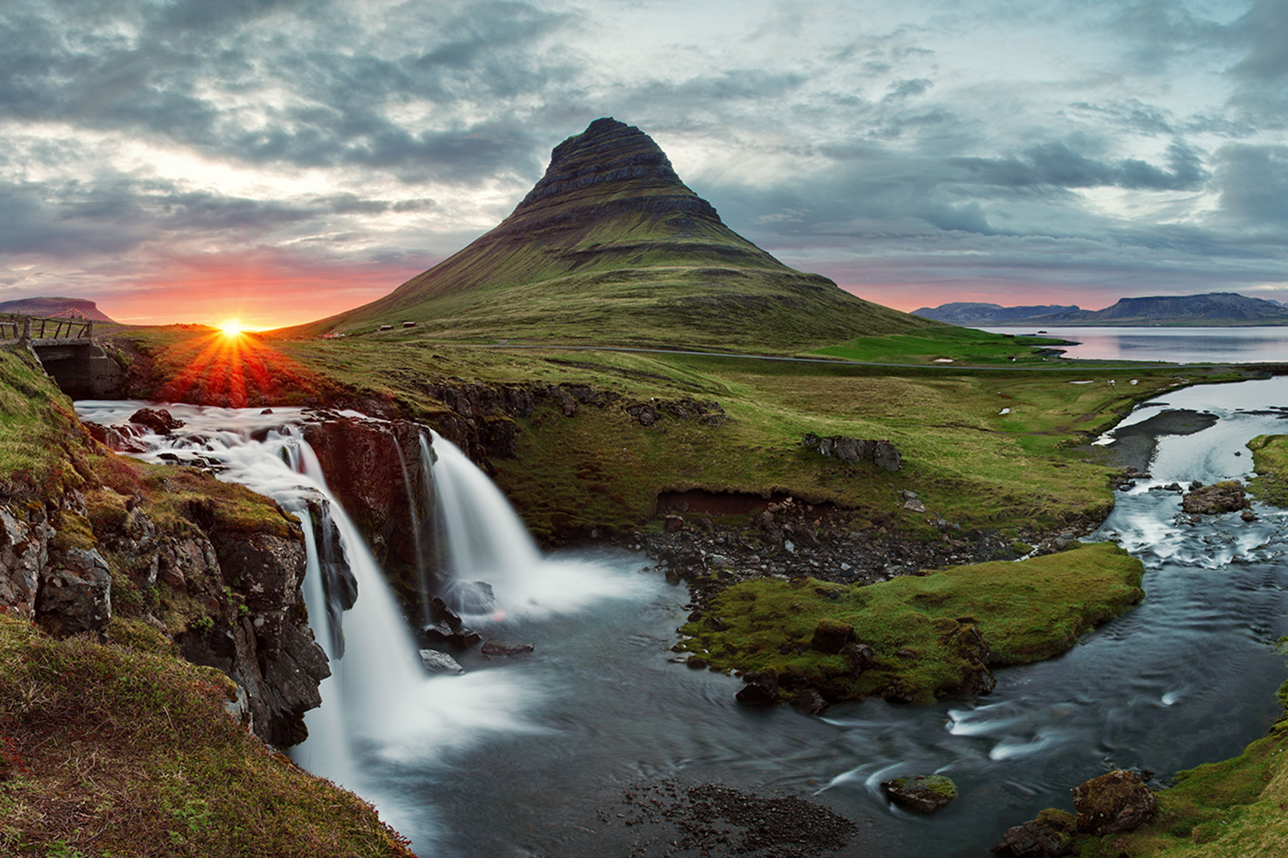 Kirkjufell and kirjufellsfoss waterfall pictured during the midnight sun with the sun setting just behind the mountain