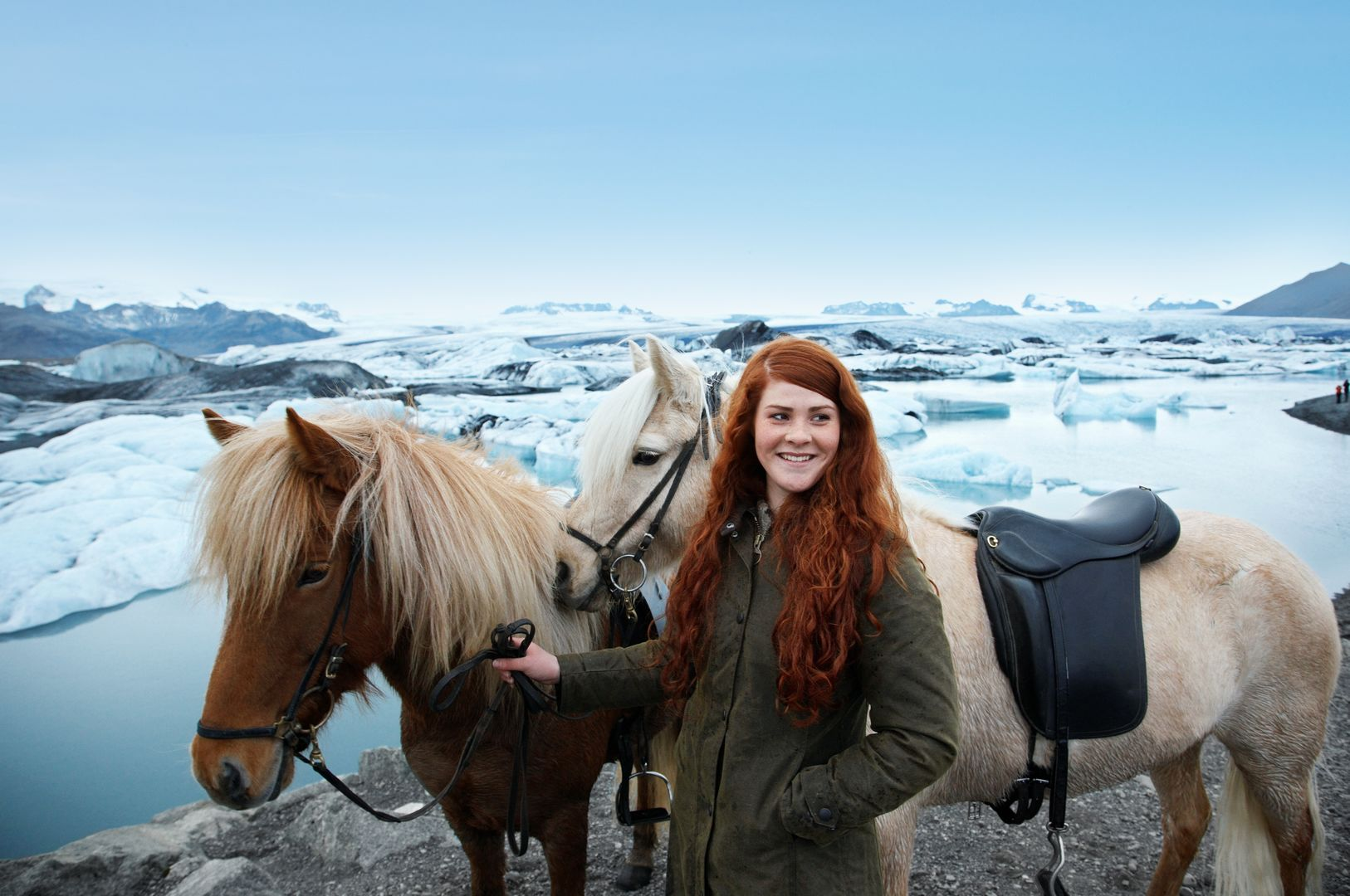 a white redhaired female smiling while standing next to two horses at Jokulsarlon glacier lagoon
