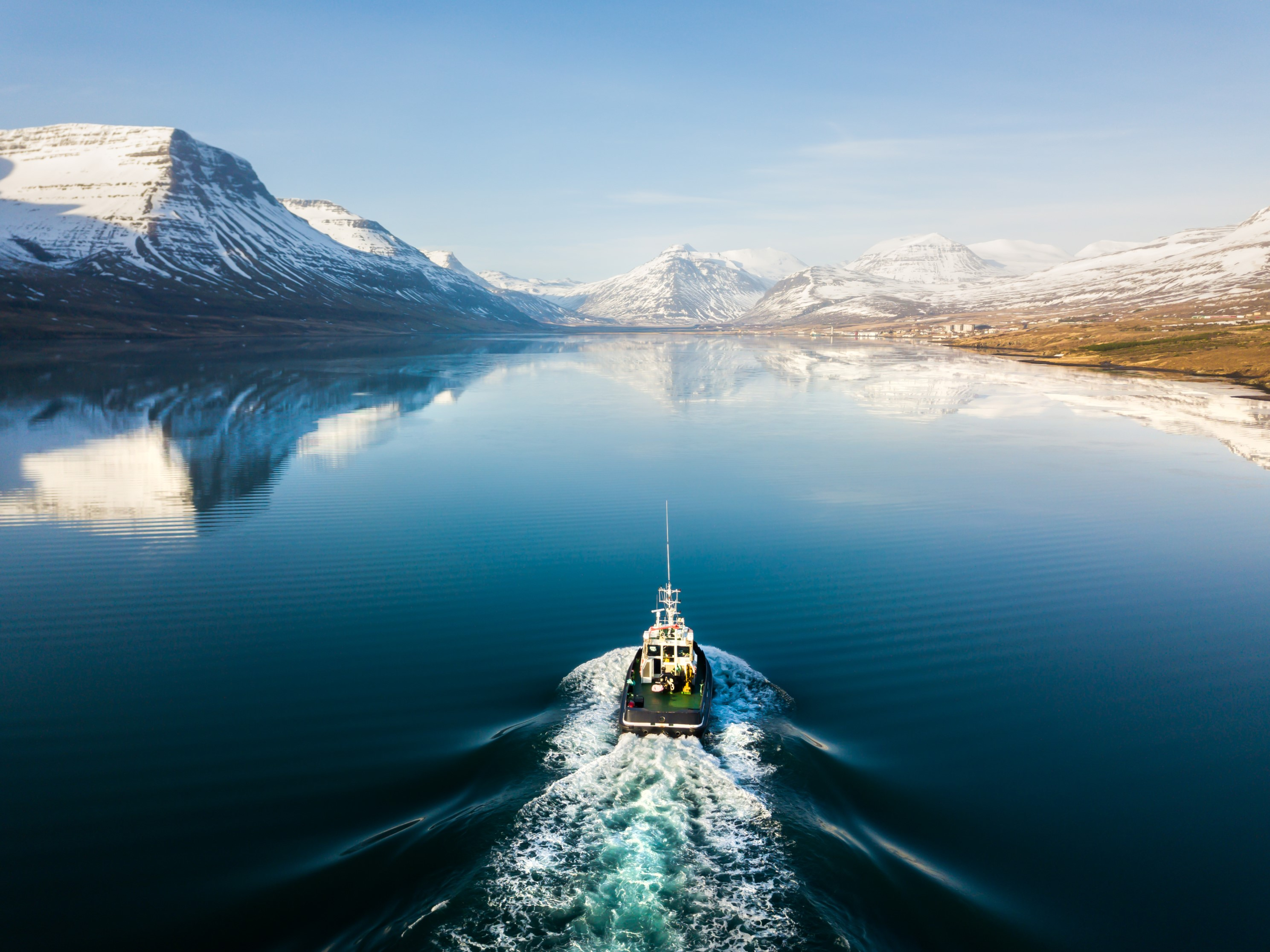 a boat sailing down a fjord in Iceland, surrounded by mountains and crystal blue sky