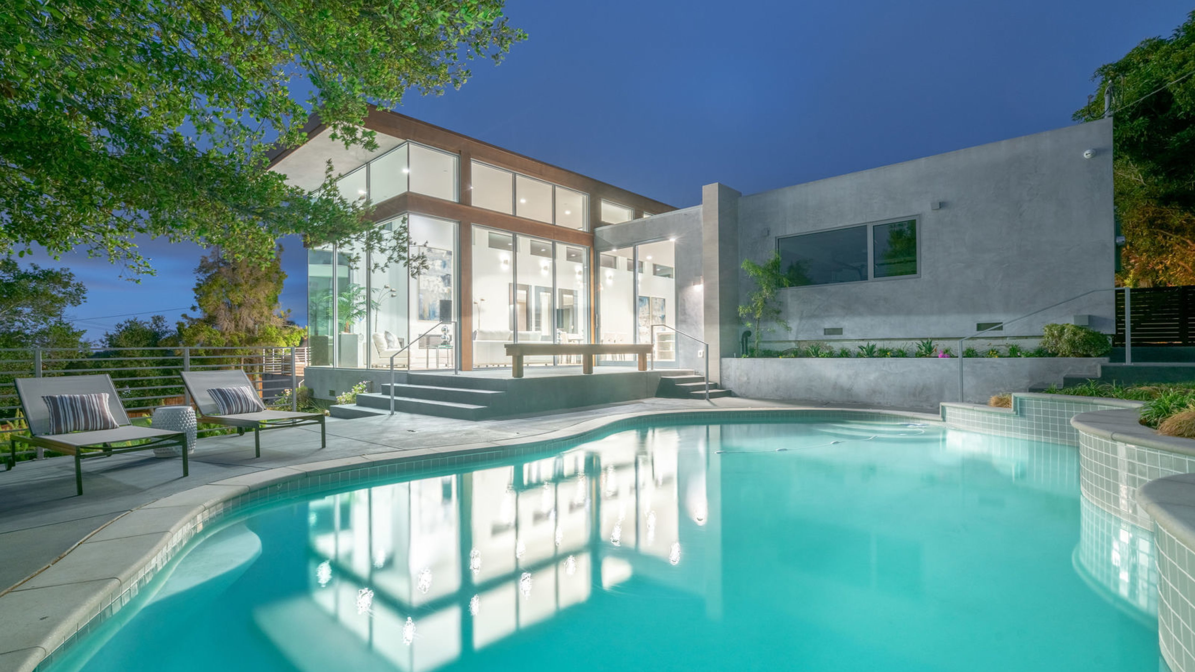 window walled home with swimming pool at dusk