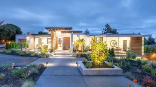 custom home exterior with aluminum windows and patio doors at dusk