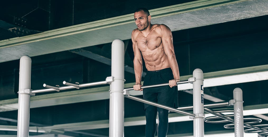 Male athlete performing dips