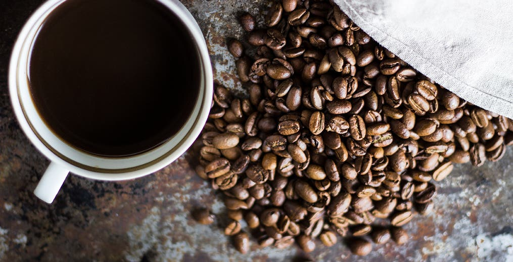 overhead shot of cup of coffee and coffee beans
