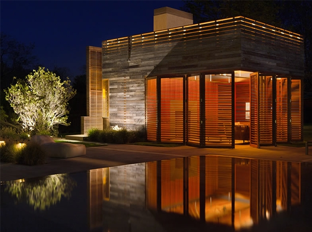 wood bifold door at night over a pool