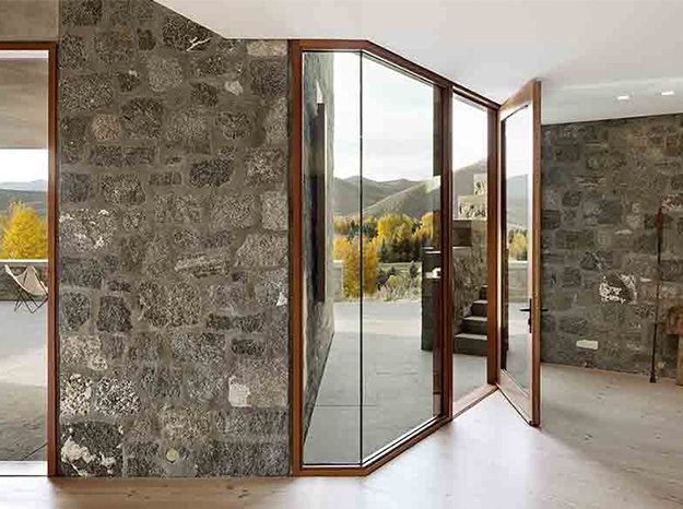 wood in-swing door on a rock wall home interior