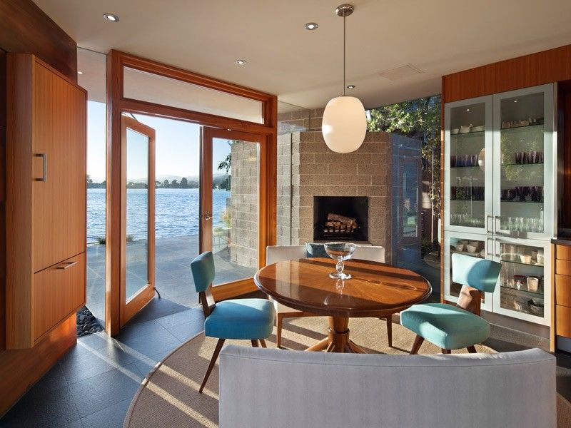 Ocean view through a slightly opened wood outswing casement door in a modern living and dining room