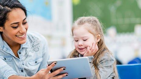 Petite fille apprenant une langue sur tablette en compagnie de son enseignante