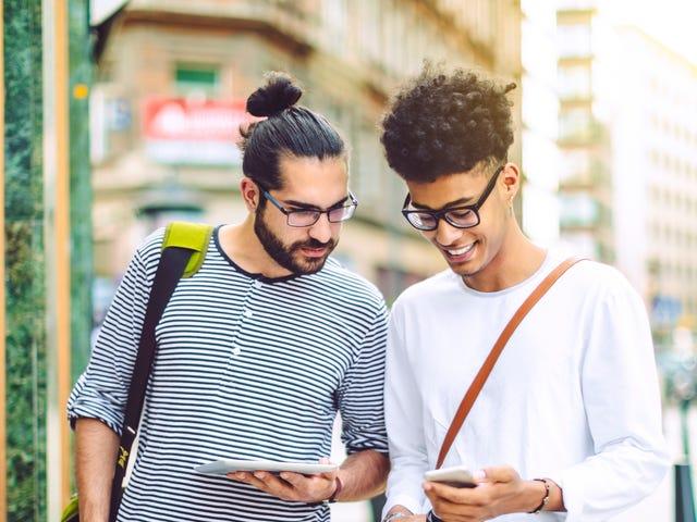 Deux jeunes hommes étudiant des langues sur smartphone