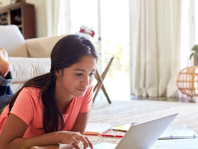 Adolescente suivant un cours de langue en ligne depuis sa chambre