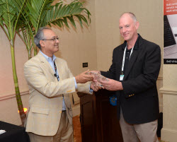 Ron Godine with TMW Systems accepts 8x8 award.