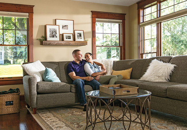 A couple sits on a couch in their living room looking out of their newly replaced windows
