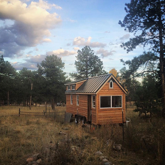 wide exterior view of a DIY tiny house in the Colorado wilderness