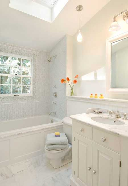 Wall-to-floor white tile in the bathroom that brightens and freshens the look