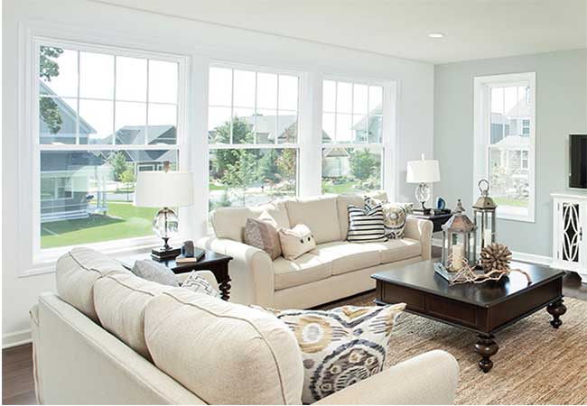 White on white furniture, windows, and walls create a sitting room fit for Joanna Gaines