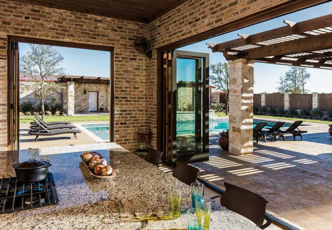 Pool view from a dining room opened up by bifold patio doors