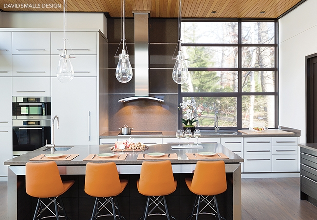 Contemporary kitchen with teardrop light fixtures hanging above center island and orange bar chairs