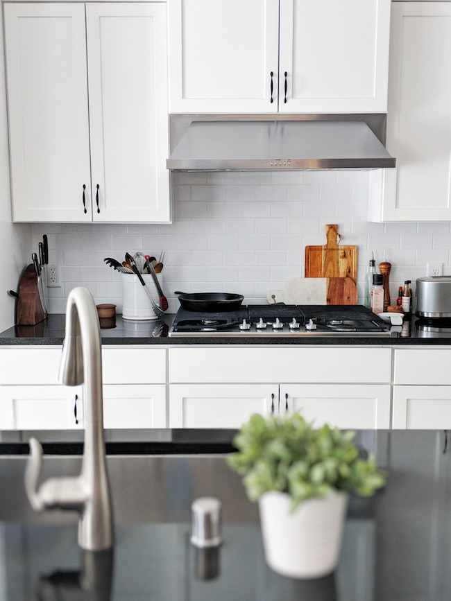 girl vs dough kitchen with white cupboards and black countertops