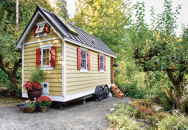 A tan-colored tiny house on a trailer amongst potted and natural plant life. Image Credit: Tiny House Living
