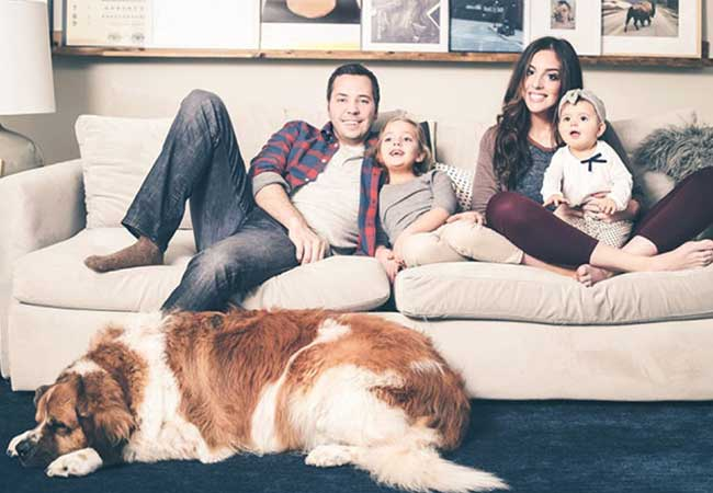Chris and Julia Marcum relax on the couch with their 2 kids and St. Bernard.