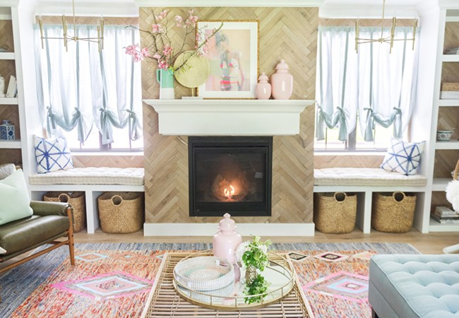 A natural wood living room with pink accents designed by blogger The Leslie Style