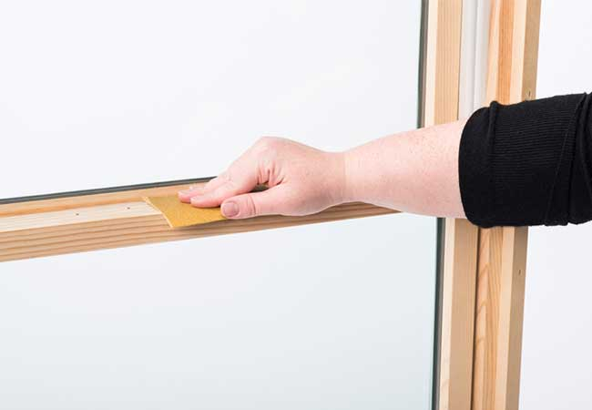 Sanding down a wood window in preparation for staining