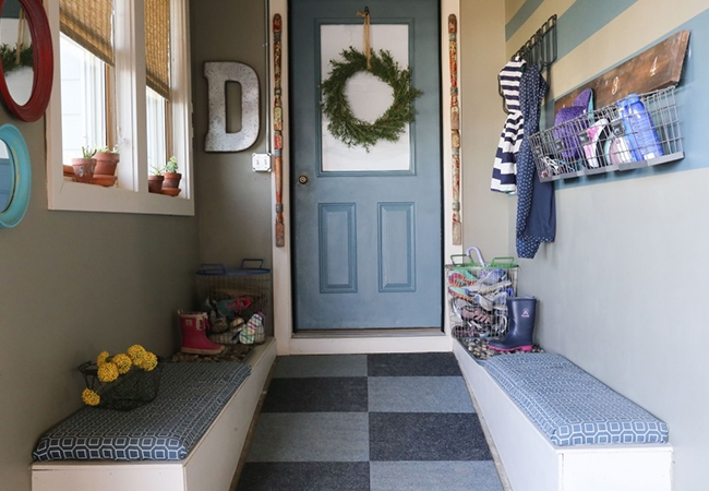 An entryway with fabric-covered benches on two walls, windows and decorative elements leading to a gray door