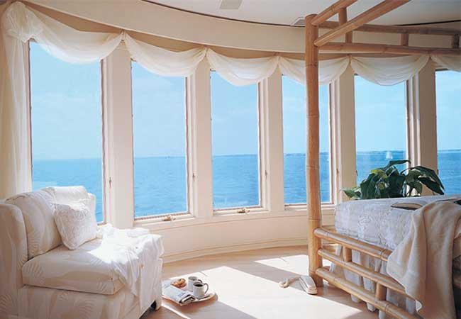 beautiful ocean view through casement window-lined wall in a master bedroom