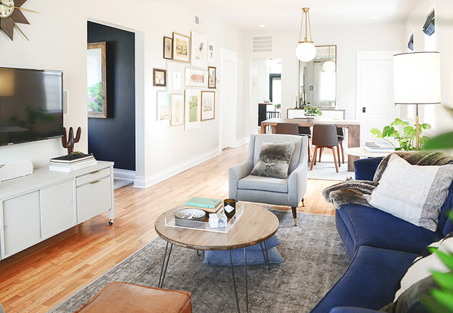 White living room with blue accents and hard wood floors by blogger yellow brick home
