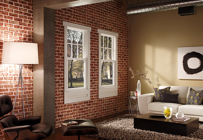 Urban-style living space with white couch, brick wall and exposed ceiling ducts