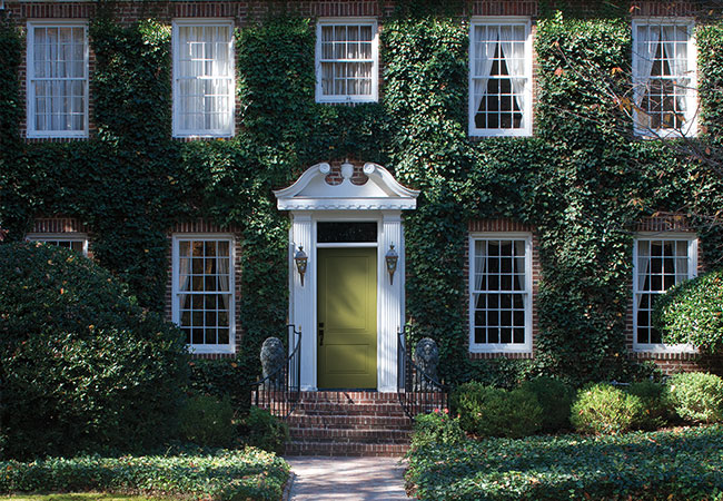 Exterior view of a brick colonial home with a green entry door