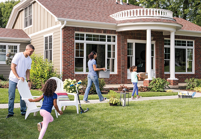 A family plays games and has fun outside of their home in summer